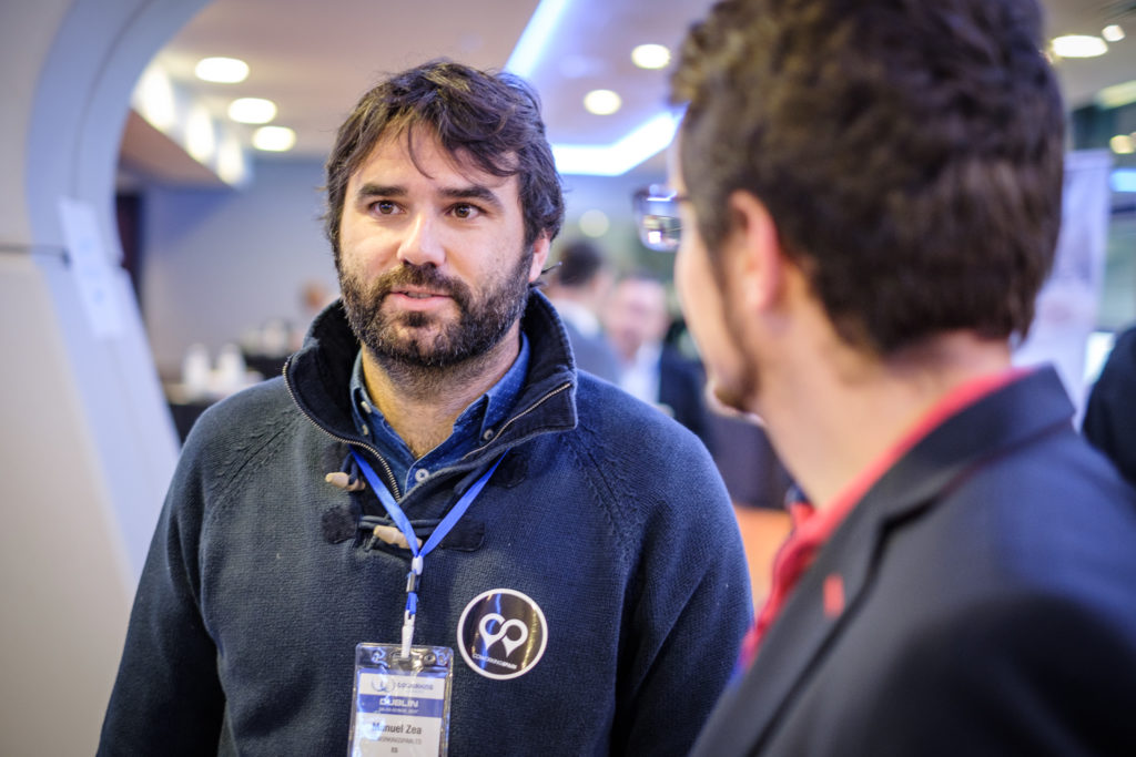Two men are talking to each other at the Coworking Europe Conference in a conference hall. The man on the right is turned away from the camera and we se only his left ear and his profile. The man on the left is Manuel Zea. He has dark hair and eyes and a short, neat, beard. He is wearing a blue shirt with a copass logo and a conference badge on a lanyard around his neck.
