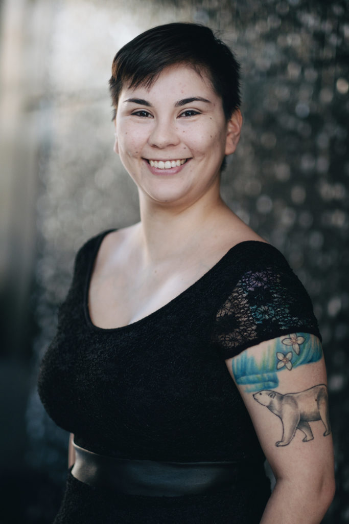 A young Indigenous woman, Tara Everett, is smiling at the camera, standing in a three quarter angle showing her left arm and full face in a formal picture.  She has short, brown hair, dark eyes, and dimples. She is wearing a black shirt with short sleeves which shows a tattoo of a bear, grass, and flowers on her left bicep.